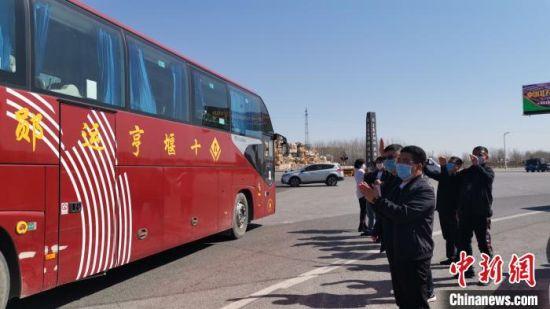 图为首批580名湖北籍务工人员抵达河北文安人造板材生产基地,当地政府、企业代表在高速口迎接。 李春梅 摄