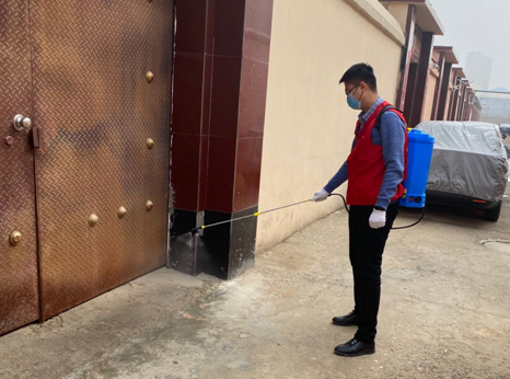 图为党员志愿者在小区内进行日常消毒工作。 韩冰 摄