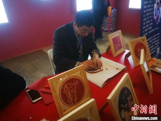 河北省阜城剪纸非遗传承人在创作剪纸文创作品。 李晓伟 摄