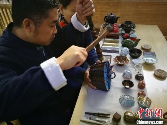 河北省非遗项目锔瓷技艺传承人在展示锔瓷技艺。 李晓伟 摄