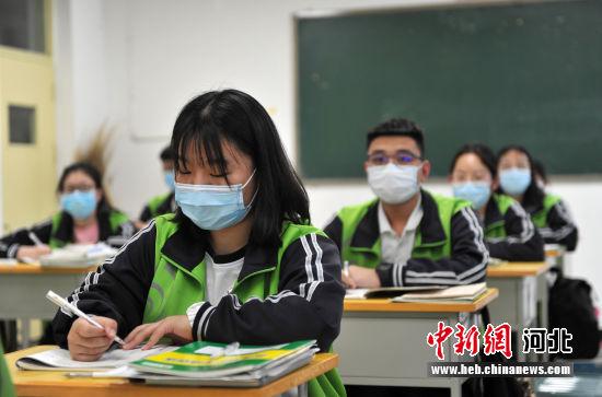图为学生佩戴口罩进行上课。