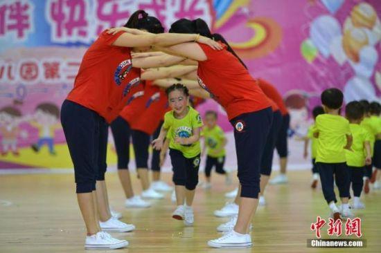 资料图:广西桂林市龙胜各族自治县民族体育馆,孩子们和家长在表演亲子操。中新社记者 潘志祥 摄
