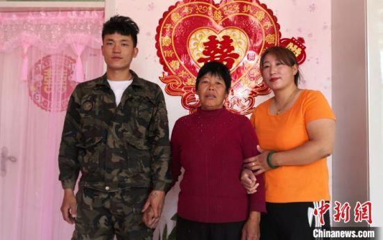 杨歌珍和儿子、儿媳在新家合影。 郭英�j 摄