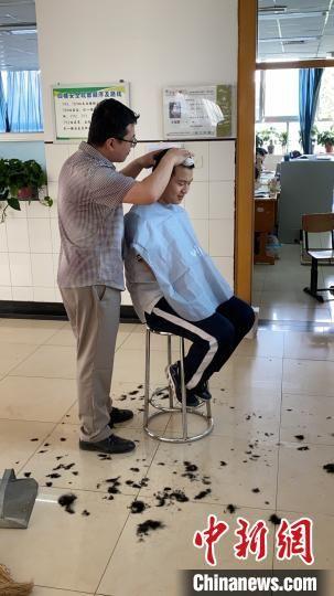 图为老师正在为学生理发。张艳春 供图