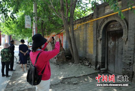 图为王晓莉对乡愁点进行拍照。 韩冰 摄