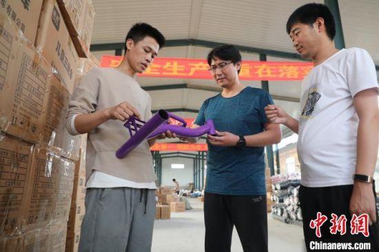 石永煊(左二)到童车玩具扶贫生产车间调研。 姚友谅 摄