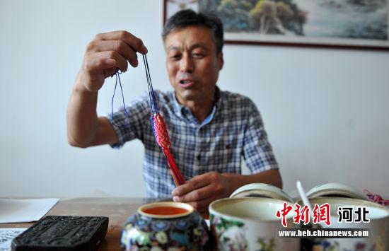 图为王勇强将香包纸放入手工编织的五彩网袋中。 韩冰 摄