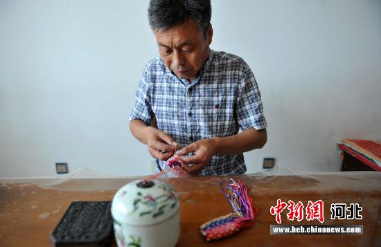图为王勇强正在编制五彩网袋。 韩冰 摄