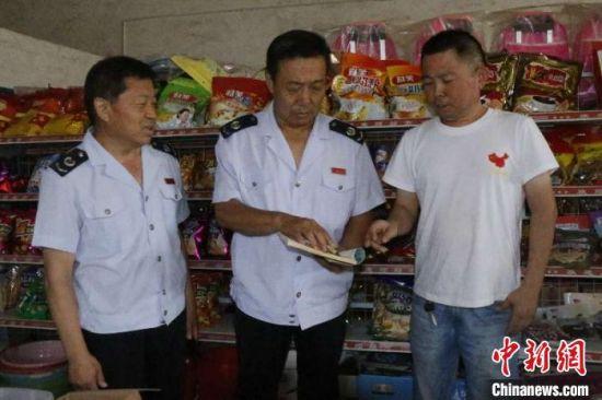 图为林长文(中)和李瑞然(左)在村里的小超市宣传税收优惠政策实施政策扶贫。 于子厚 摄