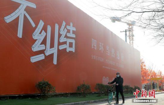 资料图:市民经过北京市丰台区樊羊路一处售楼中心。中新社记者 张宇 摄