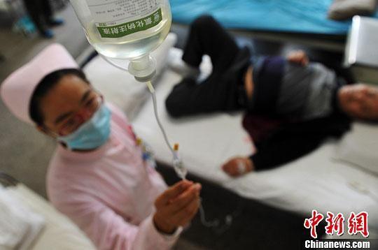 资料图:医护人员为患者输液。 翟羽佳 摄