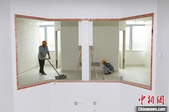 图为工人在进行地板铺装。 武殿森 摄