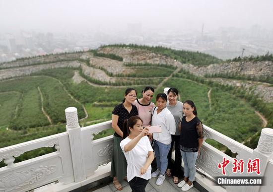 图为8月17日,市民在南响堂森林公园山顶自拍留念。中新社记者 翟羽佳 摄