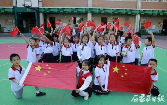 小学生与国旗合影。