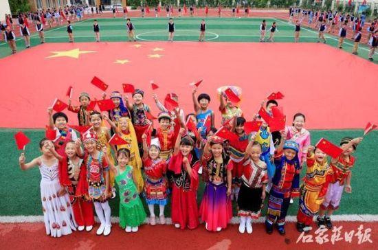 身穿民族服饰的小朋友一同祝福祖国。资料图片