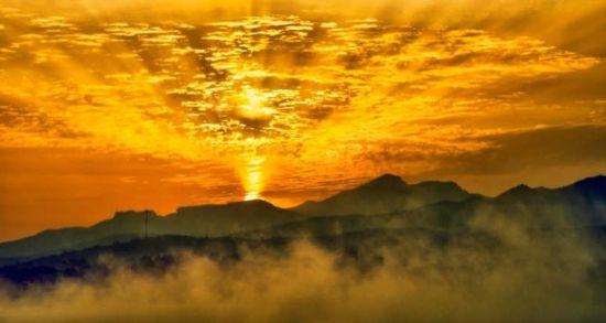 登上大坝,湖面水雾缥缈,夏季的阳光把天空映成了金色。刘静宇 摄