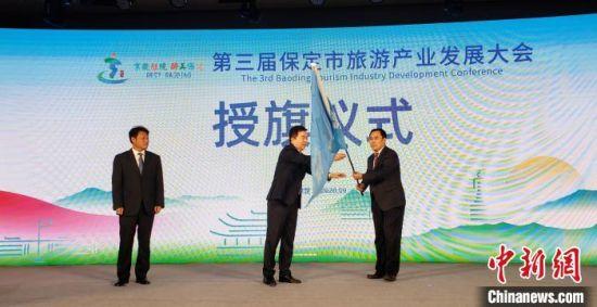 图为保定市委书记党晓龙(中)向第四届市旅发大会承办地代表安国市授旗。 徐巧明 摄
