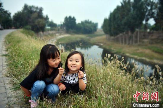 """图为位于东光县""""中国大运河・谢家坝"""",一对小姐妹正在玩耍。 翟羽佳 摄"""