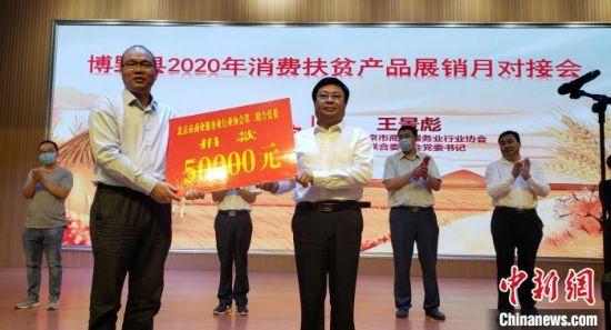 """北京市商业服务业行业协会第二联合党委向博野县捐款5万元用于扶贫励志""""暖心超市""""物品购置。 徐巧明 摄"""