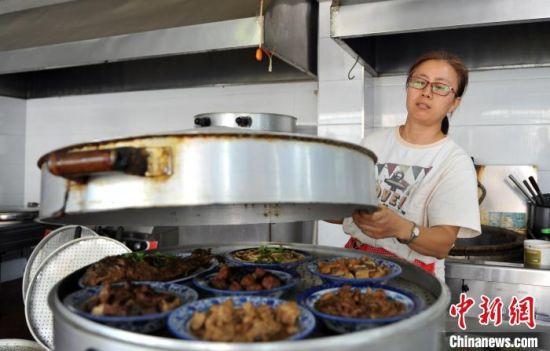 图为工作人员准备上菜。 韩冰 摄
