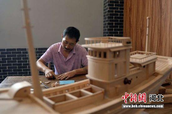 民间艺人宋树森正在制作船模。