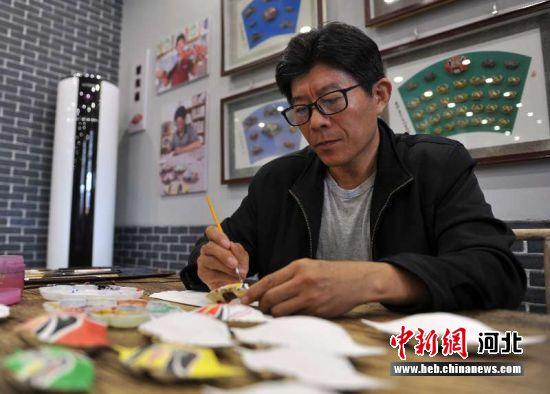 民间艺人杜宝槐正在制作蟹壳画。韩冰 摄