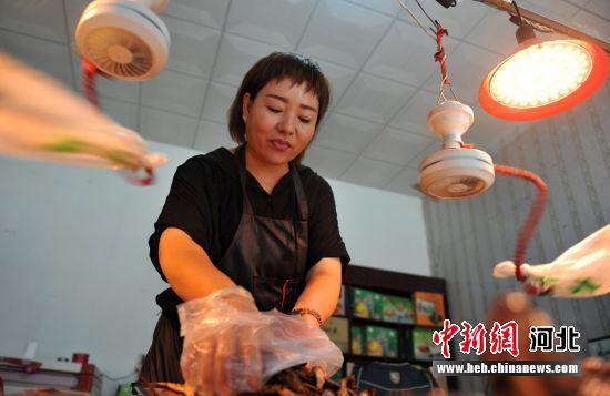 图为熏鱼店老板为客人挑选熏鱼。 韩冰 摄
