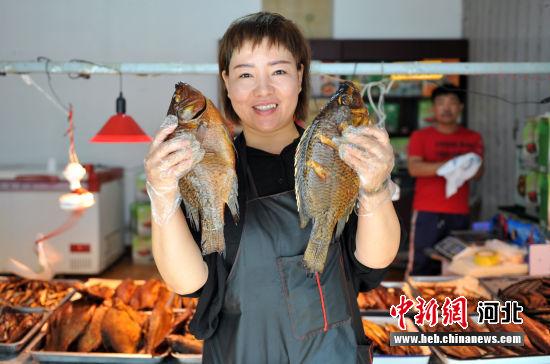 图为熏鱼店老板展示自家制作的熏鱼。 韩冰 摄