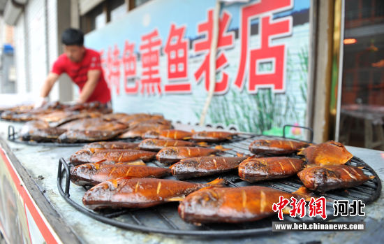 图为熏鱼老字号传承人张昆将制作好的熏鱼拿出售卖。 韩冰 摄