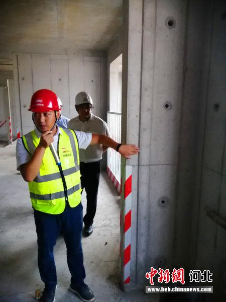 工作人员介绍安置房混凝土施工标准。 韩冰 摄