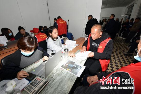 图为工作人员对搬迁户材料进行审核。 吴杰 摄