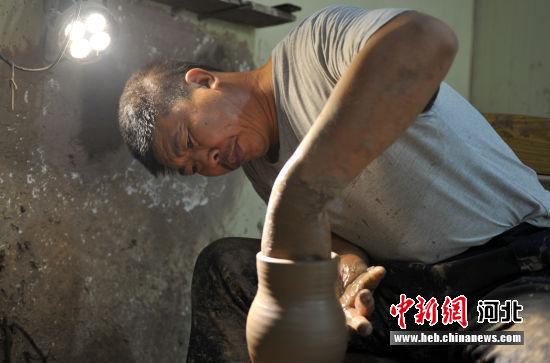 图为制作黑陶的工作人员正在进行拉坯。 韩冰 摄