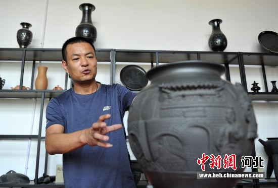 """图为刘小伟正在介绍名叫""""古韵雄安印象""""的黑陶工艺品。 韩冰 摄"""