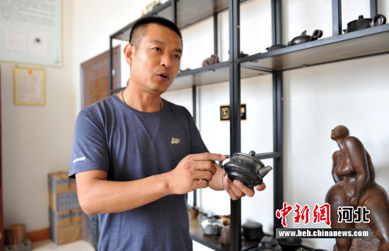 """图为刘小伟展示黑陶烧制的茶壶上的""""火痕""""。 韩冰 摄"""