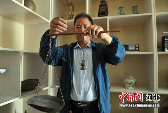 图为王艳军演示祖辈卖香肠用的秤。 韩冰 摄