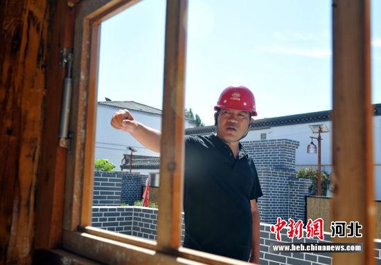 图为工作人员介绍王小燕故居改造建设情况。 韩冰 摄