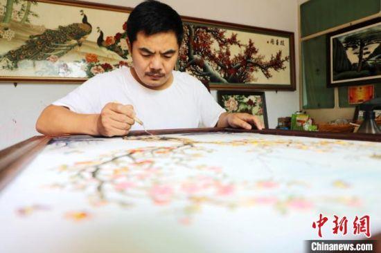 杨延刚向客户介绍景泰蓝掐丝珐琅画工艺。 姚友谅 摄