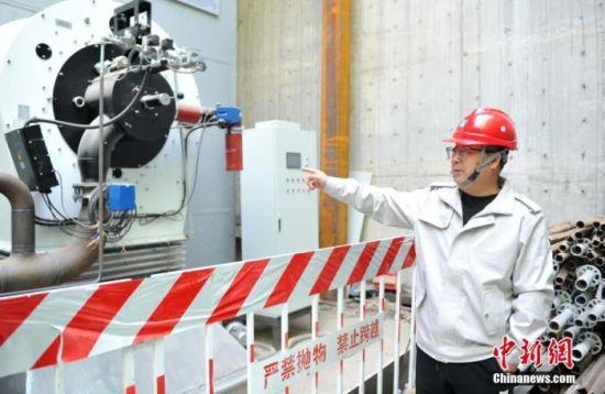 图为11月4日,中建安装集团有限公司1号能源站项目总指挥王军盛介绍燃气热水锅炉及配套余热热泵系统。 中新社记者 韩冰 摄