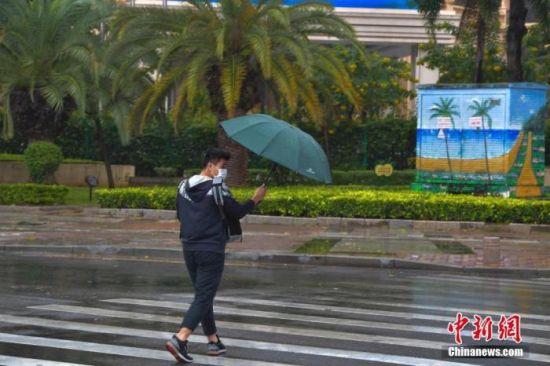 资料图:市民冒雨出行。中新社记者 骆云飞 摄