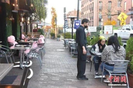 """当地时间11月9日,在美国首都华盛顿,民众在室外餐厅保持""""社交距离""""就餐。中新社记者 沙晗汀 摄"""