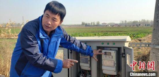 """电工王益成在讲解如何用于""""水、电一体化计量设施""""。 徐巧明 摄"""