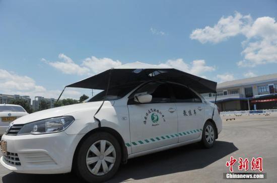 资料图:一家驾校内,学员在车顶架着遮阳蓬的教练车内练习。 中新社发 胡剑欢 摄 图片来源:CNSPHOTO