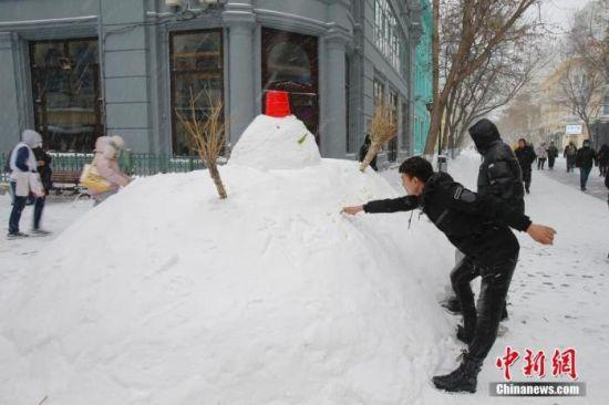 资料图:11月19日,黑龙江省哈尔滨市迎来大暴雪天气。图为中央大街上的雪人吸引游客。 中新社记者 吕品 摄