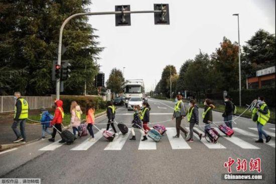 当地时间10月20日,在意大利北部贝卢斯科,孩子们拿着绳子保持社交距离,在志愿者的护送下走向学校。