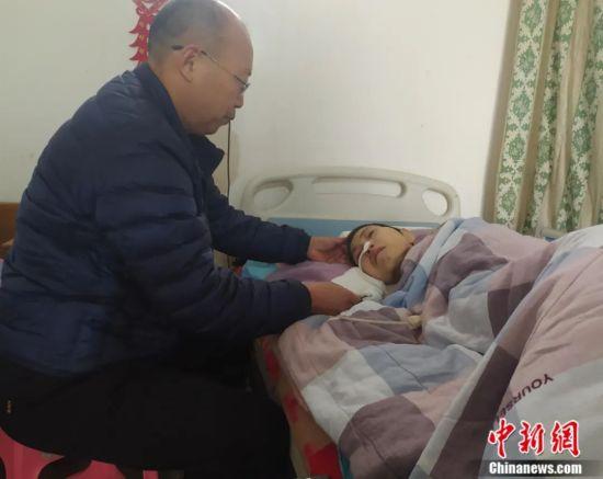 康丰民在照顾瘫痪在床的妻子。姚友谅 摄