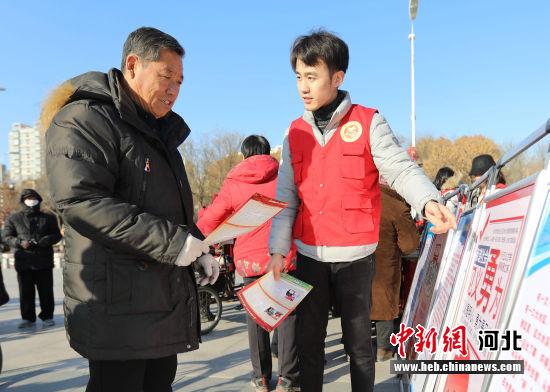 图为在河北省固安县人民广场,政法宣传干部向群众讲解见义勇为相关政策。 门丛硕 摄