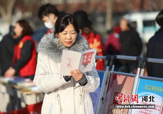 图为在河北省固安县人民广场,一名群众正浏览见义勇为相关条例。 门丛硕 摄