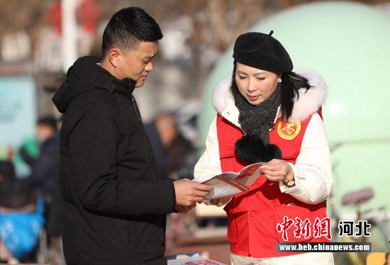 图为在河北省固安县人民广场,政法宣传干部向群众宣传讲解见义勇为常识。 门丛硕 摄