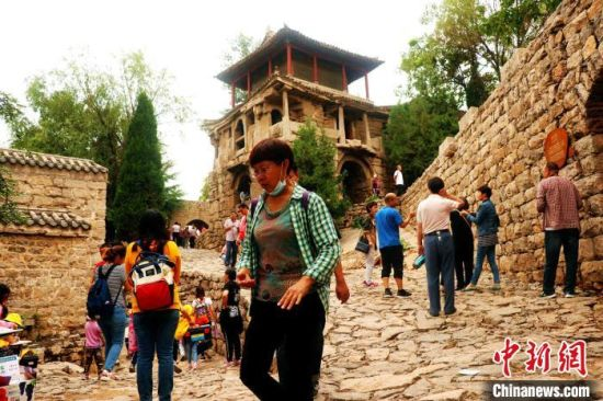 图为游客在古村落参观旅游。 段建斌 摄