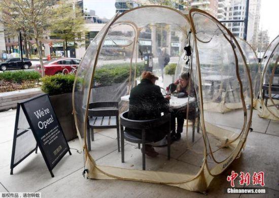"""资料图:当地时间12月18日,美国弗吉尼亚州阿灵顿市,顾客在餐厅提供的户外塑料屋里用餐,这个塑料屋被取名为""""太空泡泡屋"""",用于防止新冠病毒的传播。"""